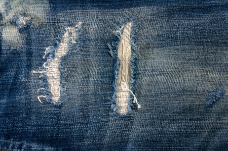 Detail of torn Blue denim, front view  jean  background or texture