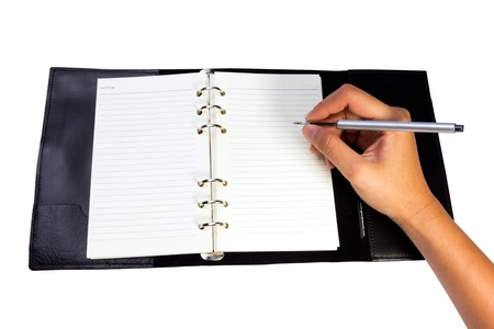 pen in hand writing on the notebook photo