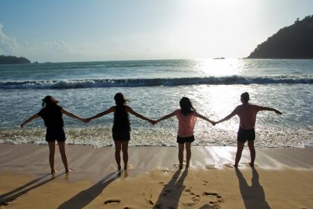 Happy jonge vrienden de groep plezier hebben en lood iemand door de hand op het strand bij de zonsondergang Stockfoto