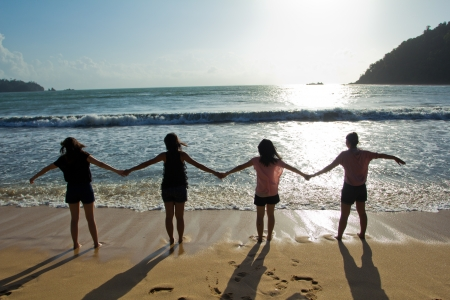 Happy young friends group have fun and lead someone by the hand on the beach at the sunset