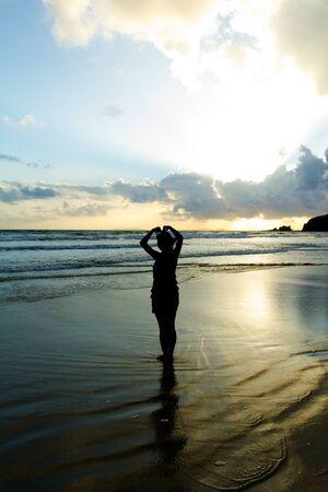 Romantische jonge Vrouw paar dat hartvorm met wapens op strand bij zonsondergang mooie hemel Stockfoto
