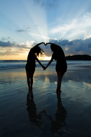 Romantic young couple making heart shape with arms on beach at sunset  beautiful sky. Stock Photo