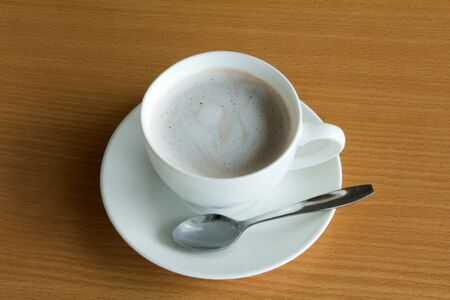 A cup of hot chocolate with cream on a wooden textured table photo