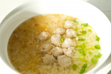 Traditional Thailand porridge rice gruel in bowl on isolated white wood background photo