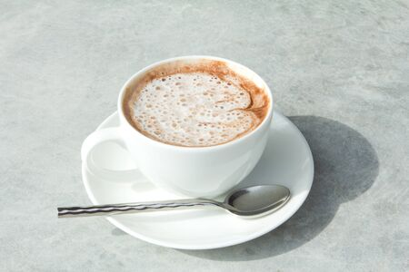A cup of hot chocolate with cream on Vintage or grungy white background of natural cement. photo