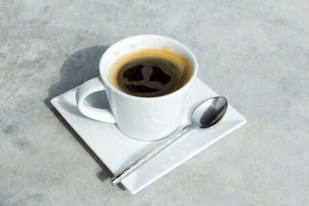 Cup of black coffee on Vintage or grungy white background of natural cement. photo