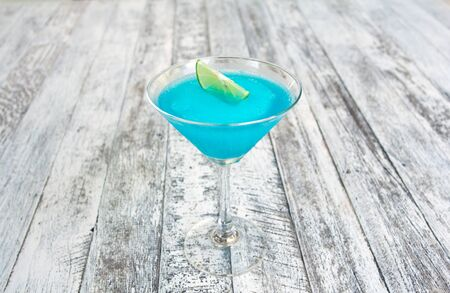 Frozen Blue Margarita Cocktail in martini glass with lemon isolated on wood table photo