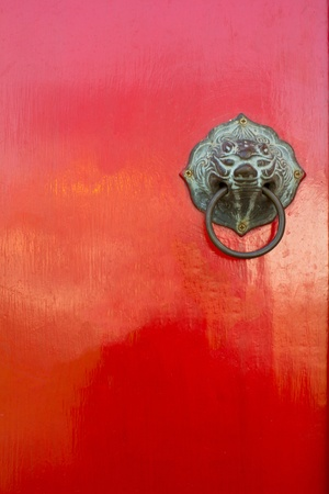 Red chinese door with a liondragon head. photo