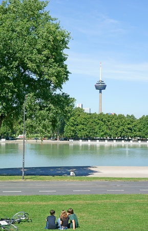 rhine westphalia: Cologne, Germany, August 23, 2012: Leisure time at a park with pond and television tower in background                             Editorial