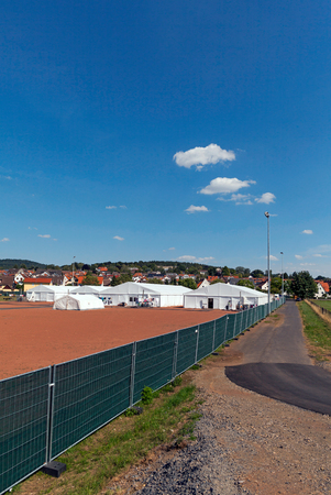 influx: Marburg, Germany - August 1, 2015: Tent camp for refugees and migrants at the football grounds at the district of Marburg Cappel.