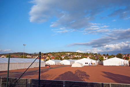 influx: Marburg, Germany - July 29, 2015: Transition tent camp for refugees and migrants at the football ground in Marburg Cappel district. Editorial
