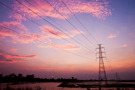 conductor electricity: High voltage pole in sunset Stock Photo