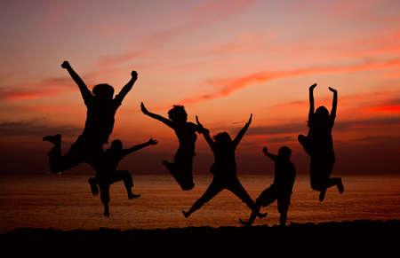 mujer hijos: Personas saltando en Playa de fondo puesta del sol Foto de archivo