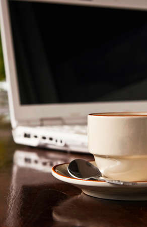 Coffee cup and notebook on wooden floor photo