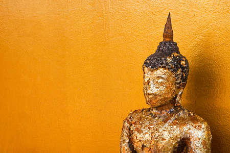 Golden buddha statue on grunge old wall photo