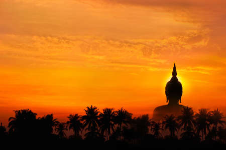 Big image buddha statue behind palm tree in sunset background