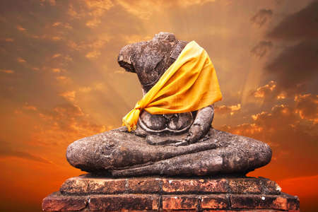 Ancient buddha statue against sunset background Stock Photo