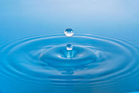 Doplets splash on clear blue water Stock Photo