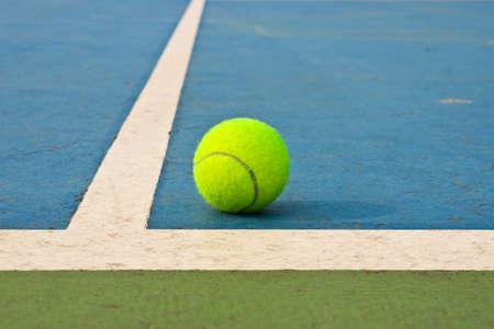 Tennis ball on blue court photo