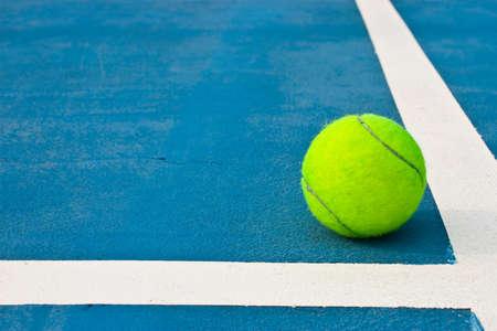 tennis courts: Green tennis ball on blue court