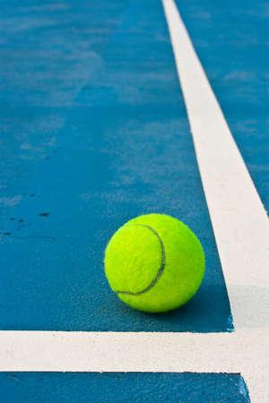 Tennis ball beside white line photo