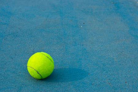 Tennis ball on blue court background photo