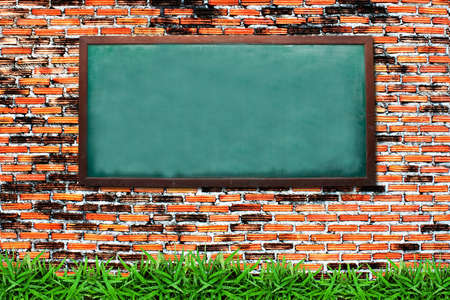 Chalkboard and green grass on grunge brick wall photo