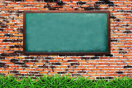 recordar: Pizarra y pasto verde en pared de ladrillo grunge