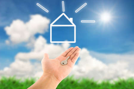 Key in hand and dream house icon, against landscape background Stock Photo - 9742773