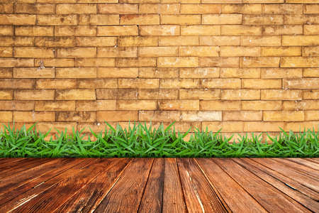 Old brick wall and green grass on wood floor photo