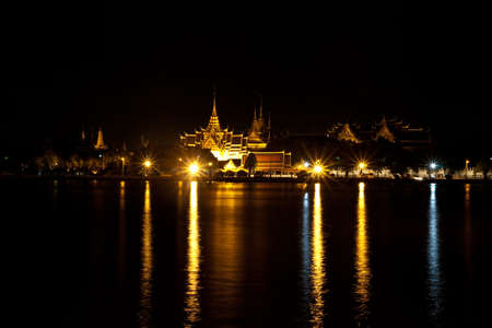 Beautiful night temple beside river in Thailand photo