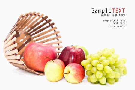 Apple and grape fruit in wooden basket, isolate on white photo