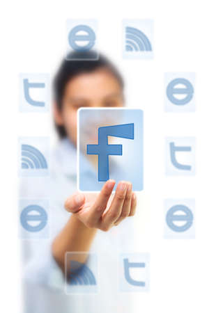 Hand holding facebook icon on touch screen pad photo