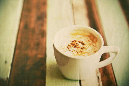 Grunge coffee cup on wood floor, vintage style photo