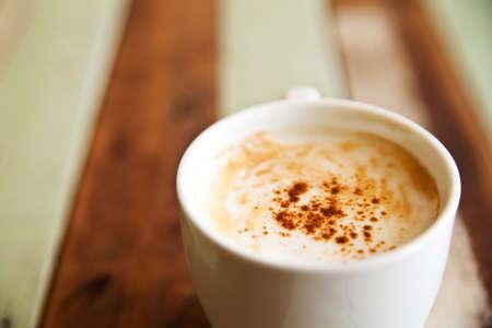 tazas de cafe: Poca profundidad de campo departamento, una taza de café sobre fondo de madera Foto de archivo