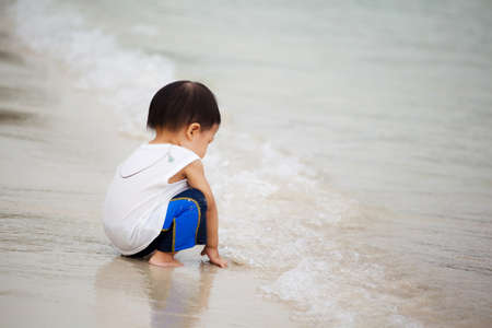 Child playing alone on the beach photo