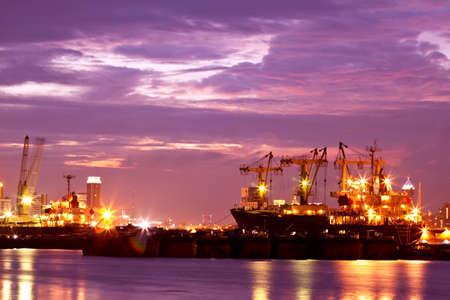 Afbeelding van de verlichte lading haven in Thailand bij zonsondergang met containerterminals, vrachtschepen en kranen bij zonsondergang achtergrond