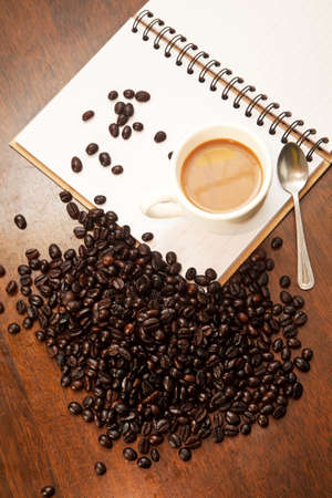 blackness: Cup of coffee on the book with beans
