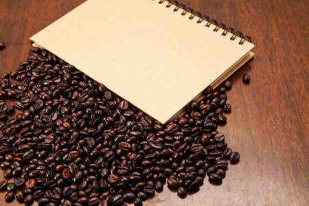 blackness: Coffee beans and book on wooden background