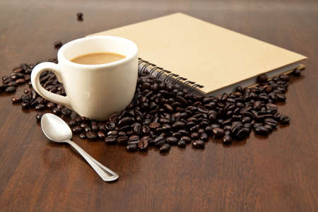 blackness: Coffee cup and book on wooden background Stock Photo