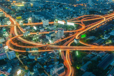 Long exposure of car light on express way cross road, Bangkok skyline in Thailand