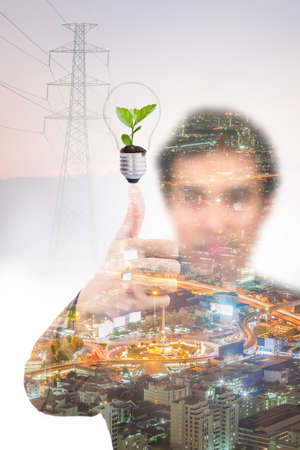 Double exposure of business man with green plant in light bulb, energy saving concept