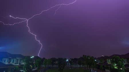 Lightning bolt during raining storm over home garden