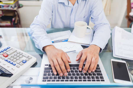 Business man typing laptop keyboard during working in office