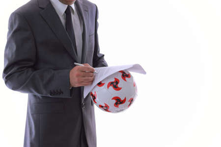 a man in suit signing a transfer contract on the ball photo