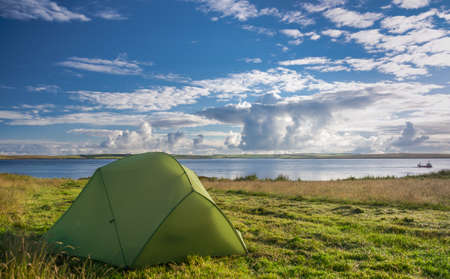 a pitched tent near lake on sunny day photo
