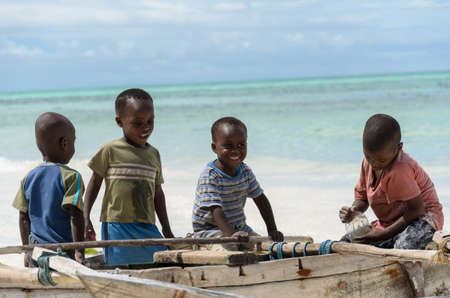 TANZANIA, ZANZIBAR: MARCH 26 2013: young happy african boys on fishing boat waiting for parents