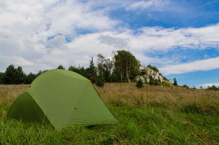 camping pitch: pitched tent in meadow with big rock