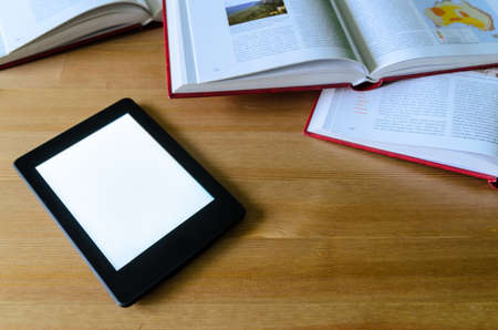compared: lightweight e-book (electronic reader) compared to heavy thick books - stock photo Stock Photo