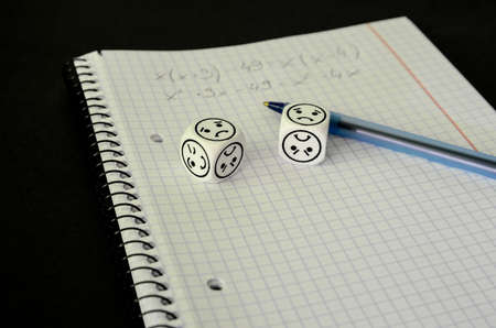 exercise book with mathematical equation and dices with sad face on black background